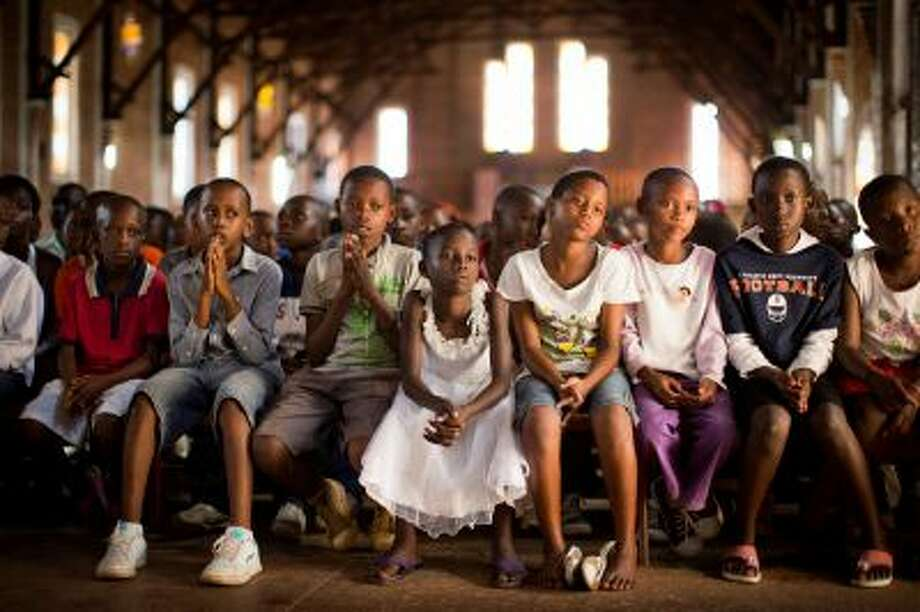 Rwandan children listen and pray during a Sunday morning service at the Saint-Famille Catholic church, the scene of many killings during the 1994 genocide, in the capital Kigali, Rwanda Sunday, April 6, 2014. Rwanda will commemorate on Monday the 20-year anniversary of the genocide when ethnic Hutu extremists killed neighbors, friends and family during a three-month rampage of violence aimed at ethnic Tutsis and some moderate Hutus, leaving a death toll that Rwanda puts at 1,000,050. (AP Photo/Ben Curtis) Photo: AP / AP2014