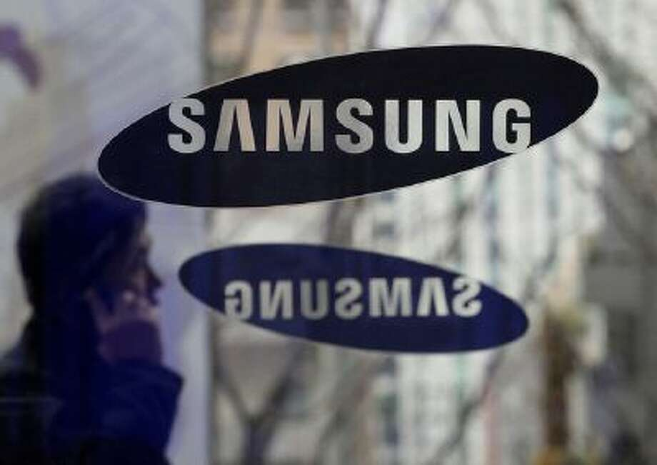 File - In this Dec. 12, 2013 file photo, a man passes by the Samsung Electronics Co. logos at its headquarters in Seoul, South Korea. Opening statements are underway in the latest patent fight over mobile devices between Apple and Samsung, the world's largest cellphone manufacturers. An Apple lawyer told jurors in San Jose, Calif., on Tuesday April 1, 2014, that Samsung quickly recognized that the iPhone was going to be a big seller when it first went on the market, and the South Korean company didn't have a product that could compete. (AP Photo/Ahn Young-joon, File) Photo: AP / AP net