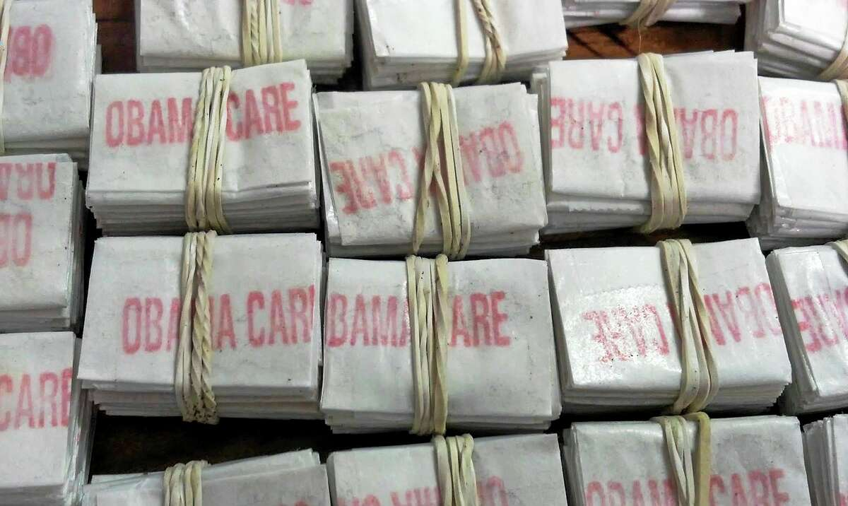 """FILE - This photo released on Friday, Dec. 20, 2013 by the Massachusetts State Police shows some of the 1,250 packets of heroin labeled """"Obamacare"""" and """"Kurt Cobain"""" which state police troopers confiscated during a traffic stop in Hatfield, Mass. Four people were charged with heroin trafficking. (AP Photo/Massachusetts State Police)"""