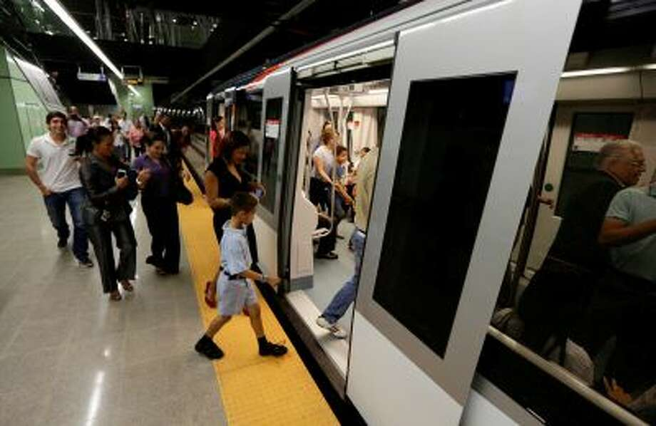 In this Wednesday, April 2, 2014 photo, government employees and their guests enter a subway while participating in an invitation to test the wagons of the new Panama Metro in Panama City. Central America's first underground metro will surely alleviate the booming capital's dreadful traffic. But critics say the $2 billion spent on the 14-kilometer rail project, which was marred by cost overruns, would've been better used building a higher-capacity, surface transport network. They also are blasting the timing of the over-the-top inauguration set for Saturday, April 5, which they say is a political stunt by President Ricardo Martinelli to drum up support for his preferred successor. (AP Photo/Arnulfo Franco) Photo: AP / AP