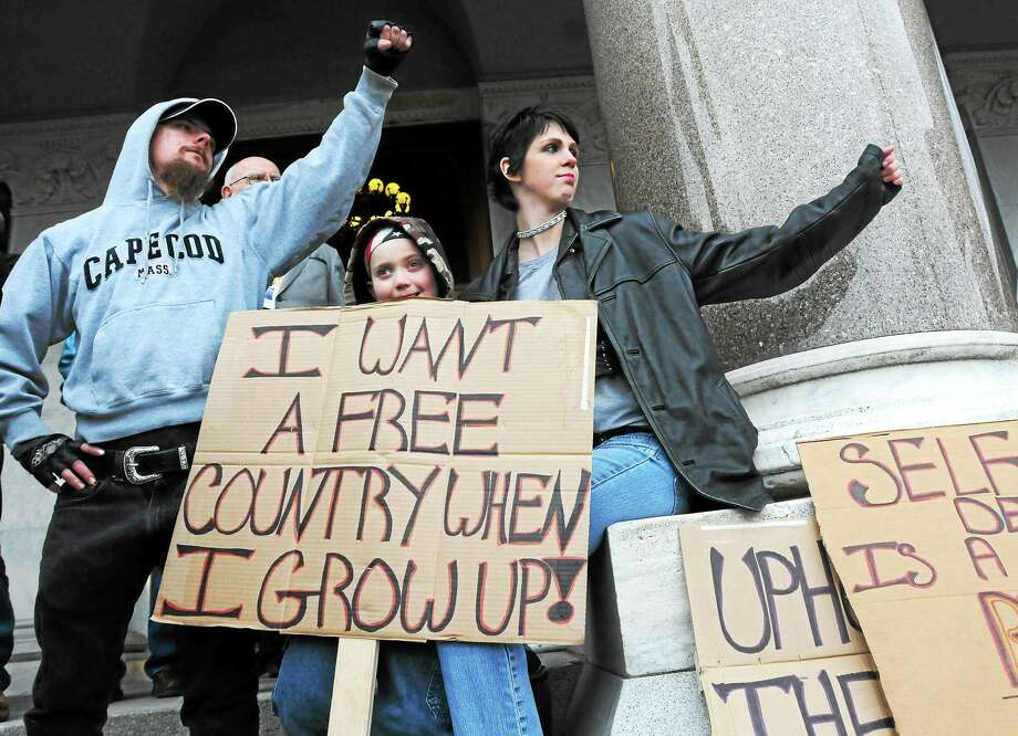 (Peter Hvizdak - New Haven Register) William Rhoades (CQ) of Tolland, Connecticut, left, with his son Ethan Rhoades, 9, and wife Crystal Rhoades, right, at the Connecticut Citizen Defense League sponsored pro-gun rights rally Saturday April 5, 2014 at the State Capitol in Hartford, Connecticut. Approximately 1500 people attended  including participation of supporters from New England states, New York, and Montana. The rally marks one-year since Governor Malloy signed a ban and assault rifles and standard capacity magazines over 10-rounds. Photo: New Haven Register / ©Peter Hvizdak /  New Haven Register