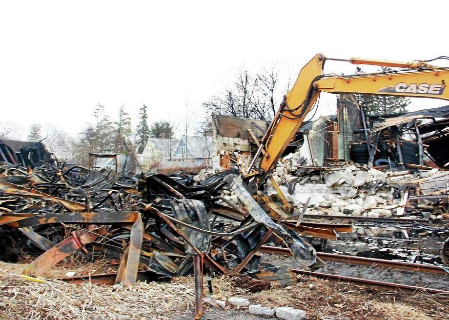 The charred wreckage of the large five-alarm fire on Friday, April 4, 2014, in Torrington. Firefighters fought the blaze for nearly 10 hours and stayed on site for 21, as the last six firefighters left the scene early Friday morning. Photo: Esteban L. Hernandez — Register Citizen