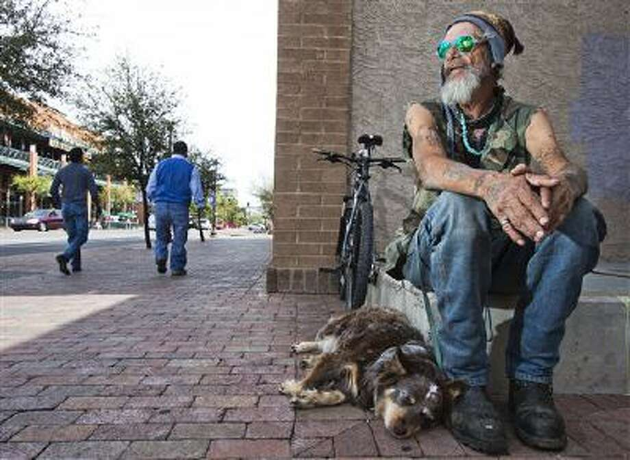 """Dave """"Stickman"""" Cortiana sits at Fifth Street and Maple Avenue in Tempe with his dog, Ruby. Cortiana says he has been told by Tempe police that he can't sit on Mill-area sidewalks. (AP Photo/Tom Tingle, The Arizona Republic) Photo: AP / The Arizona Republic"""