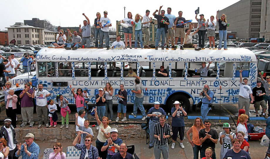UConn fans wave to the teams as they stand on top of a bus that they painted throughout the night during a joint parade in Hartford for the men's and women's college basketball national champions on April 18, 2004. Photo: Steve Miller — The Associated Press File Photo  / AP
