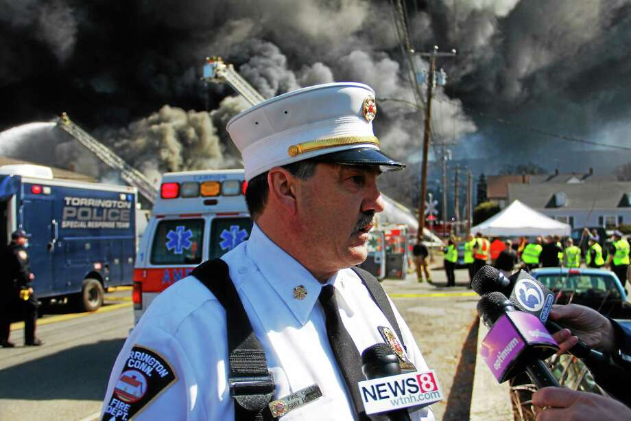 Chief Gary Brunoli talks with reporters as Torrington and dozens of other departments battle a five-alarm blaze at Toce Brothers Inc., a warehouse full of tires, on Albert St in Torrington. Photo: Esteban L. Hernandez — The Register Citizen