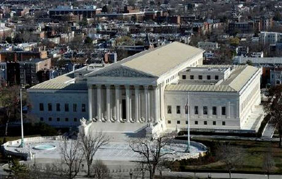 FILE - This Dec. 19, 2013, file photo shows a view of the Supreme Court from near the top of the Capitol Dome on Capitol Hill, in Washington. The Supreme Court is hearing arguments in a case that asks whether a victim of child pornography can seek millions of dollars from a defendant who had just two images of her on his computer. The woman known only as Amy is trying to persuade the justices in arguments on Jan. 22, 2014, that people convicted of possessing child pornography should be held liable for the entire cost of the harm their victims suffer, including in psychiatric care, lost income and legal fees.  (AP Photo/Susan Walsh, File) Photo: ASSOCIATED PRESS / A2013