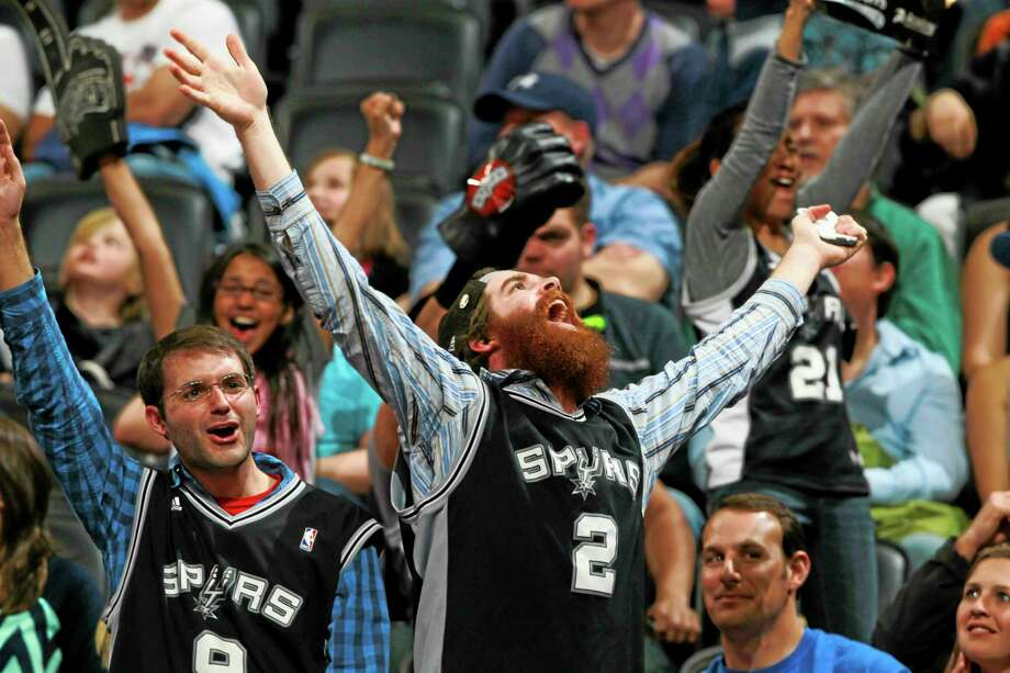 San Antonio fans cheer as time runs out in the Spurs' 133-102 victory over the Nuggets on Friday in Denver. Photo: David Zalubowski — The Associated Press  / AP