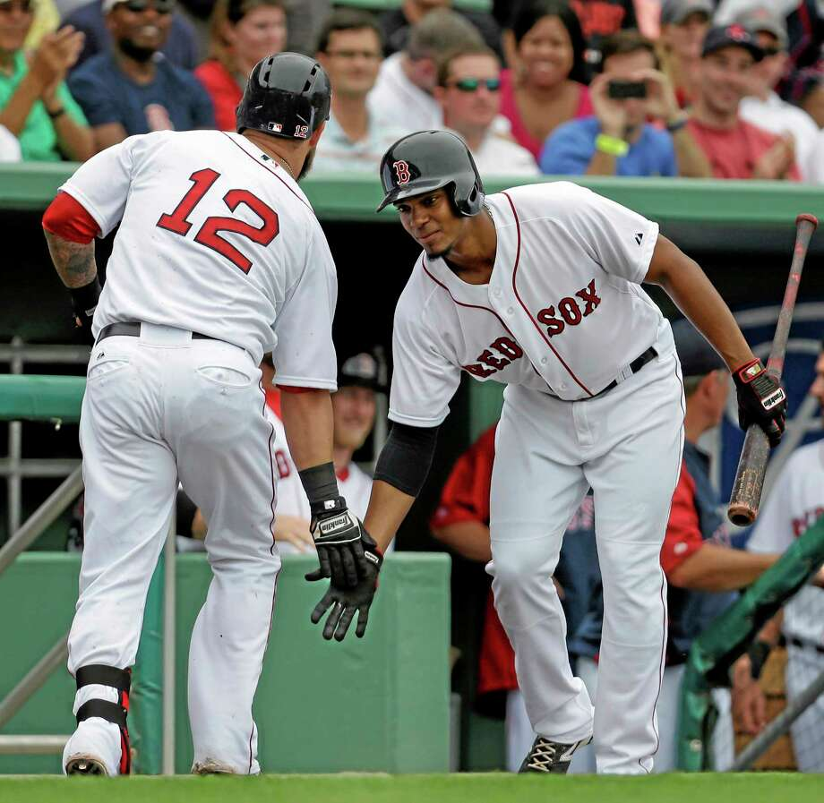 Boston Red Sox shortstop Xander Bogaerts greets first baseman Mike Napoli (12) after Napoli's solo home run during a spring training game against on Saturday. Bogaerts is the second-ranked prospect in baseball. Photo: Gerald Herbert — The Associated Press  / AP