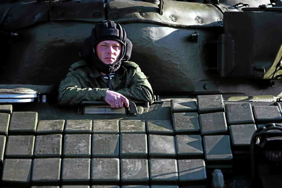 Russian solder sits in the tank T-72B at the Ostryakovo railway station not far from Simferopol, Crimea, Monday, March 31, 2014. Russian tanks T-72B will be stationed on former Ukrainian military bases. (AP Photo/Pavel Golovkin) Photo: AP / AP