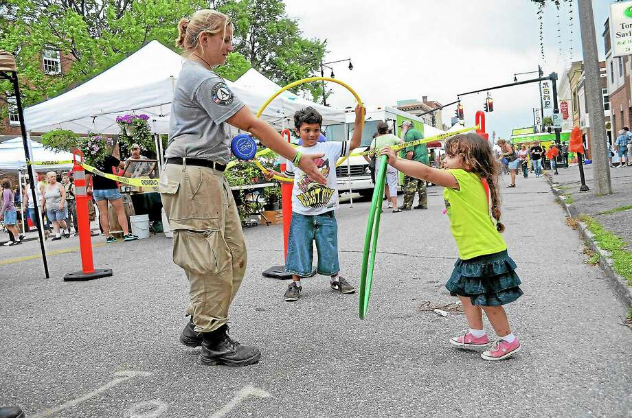 Emmy, 3, and Eric, 8, De La Cruz try out the hula hoops with Sarah Kolb of Americorps' National Civilian Community Corps during Thursday night's Main Street Marketplace. Photo: John Berry — Register Citizen