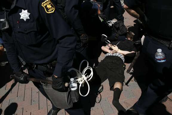 A protester is detained by Berkeley police after an angry crowd followed three conservative rally attendees, before pushing them out of the park in Martin Luther King Jr. Civic Center park August 27, 2017 in Berkeley Calif.