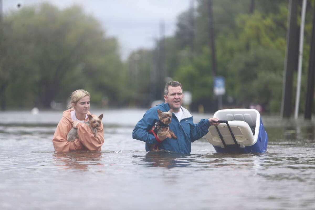 People walk out of their flooded Meyerland streets, Sunday, August 27, 2017.