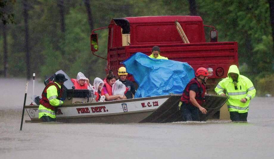 Porter fire fighters evacuate a family by boat from a neighborhood off East Knox Drive, Sunday, Aug. 27, 2017, in Porter. Photo: Jason Fochtman, Staff Photographer / © 2017 Houston Chronicle