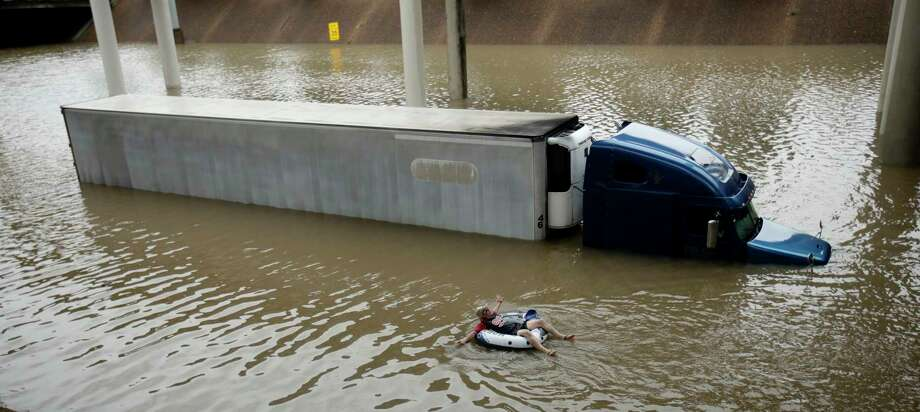 After helping the driver of the submerged truck get to safety, a man floats on the freeway flooded by Tropical Storm Harvey on Aug. 27, near downtown Houston.  Photo: Charlie Riedel, Associated Press / Copyright 2017 The Associated Press. All rights reserved.