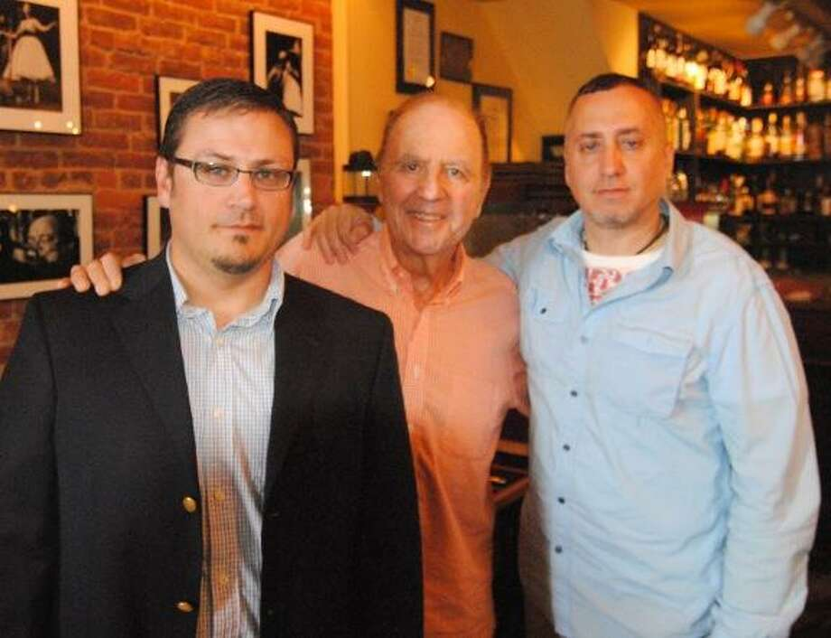 "MIKE AGOGLIATI/ Register Citizen West Street Grill co-owner Charlie Kafferman stands with writer and director of Brilliant Mistakes"", Paul Brighton, right and producer Tim Forry, left. Kafferman opened up his restaurant for filming early Wednesday."