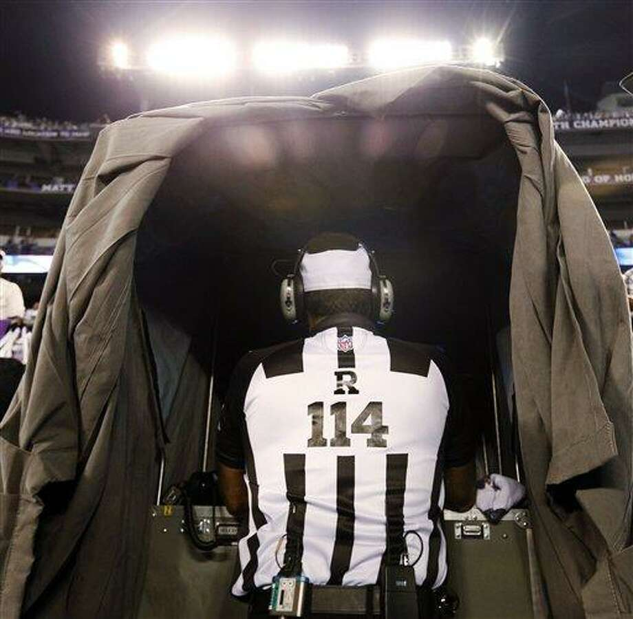 Referee Gene Steratore looks over the instant replay monitor before an NFL football game between the Baltimore Ravens and Cleveland Browns in Baltimore, Thursday, Sept. 27, 2012. (AP Photo/Patrick Semansky) Photo: AP / AP
