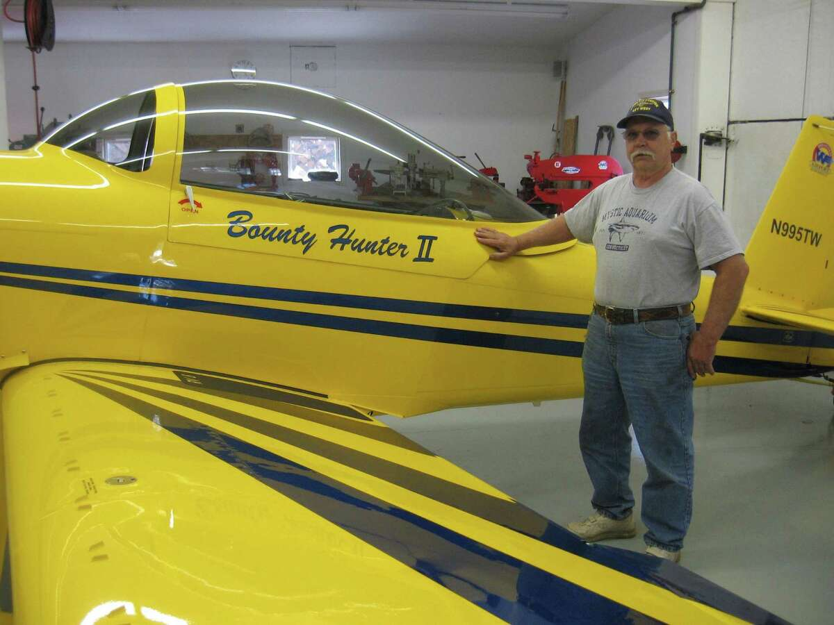 Tom Whelan with the Bounty Hunter II plane that he built a hangar at his private airport in Bethlehem.