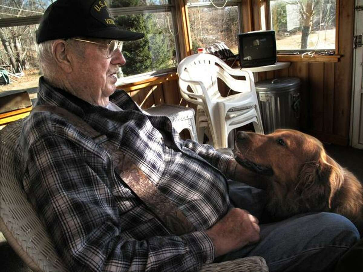 DEBBI MORELLO/Register Citizen U.S. Navy veteran George Coleman of Robertsville with his dog at home last week. Coleman, a World War II and Korean War veteran, shared his time at war with The Register Citizen's reporter Debbi Morello.