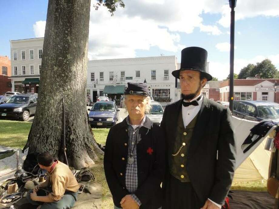 """JASON SIEDZIK/ Register Citizen Louis Dube, right, presented himself as President Abraham Lincoln's  for Borough Days on Sunday. He was joined by a member of the CT Artillery Regiment, which hosts an encampment on the Litchfield Green during the annual event. To purchase this picture, visit <a href=""""http://registercitizen.com"""">registercitizen.com</a>."""