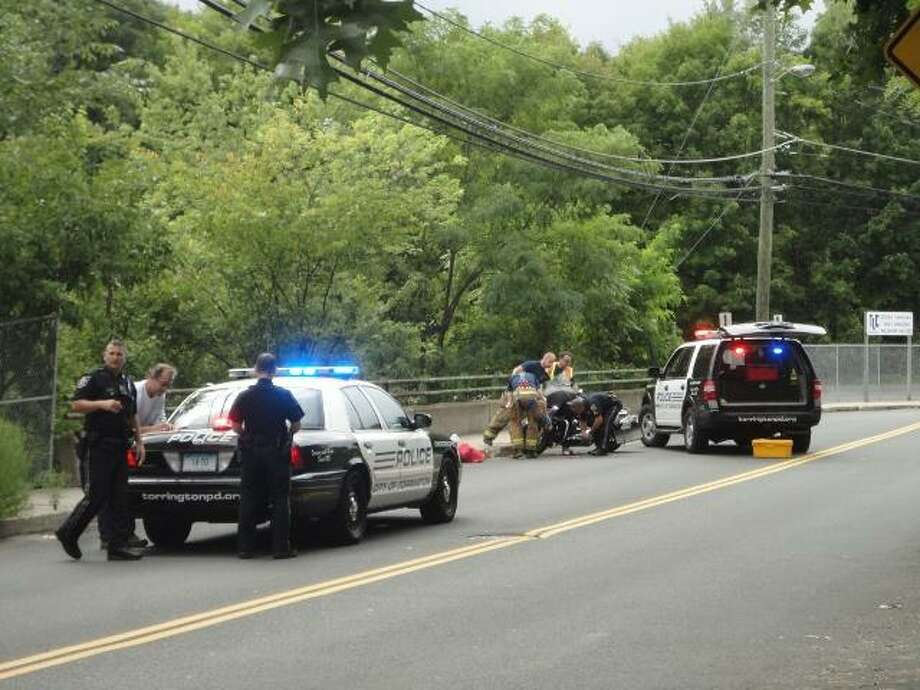 """JASON SIEDZIK/ Register Citizen Torrington police officers attend to the scene of a one-motorcycle accident on Church Street, which occurred at the bridge over the Naugatuck River. The accident occurred at 3:16 p.m. on Sept. 3 and closed the street for roughly one hour. The lone victim in the accident, 52-year-old Perry Polderman of Norfolk, was taken to Charlotte Hungerford Hospital, and his status was not available at press time. To purchase this photo visit <a href=""""http://registercitizen.com"""">registercitizen.com</a>."""