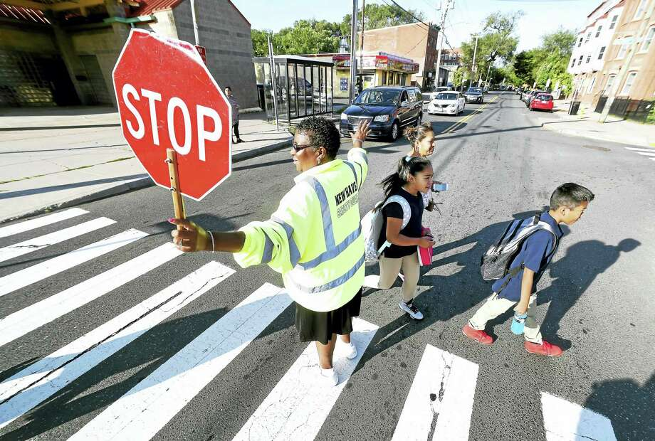 Crossing guard Annette Cox stops traffic on Congress Avenue for children to cross on the first day of school at John C. Daniels School of International Communications in New Haven. Photo: Arnold Gold / Hearst Connecticut Media / New Haven Register
