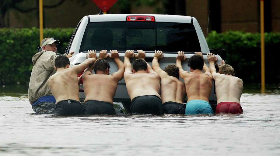 People push a stalled pickup through a flooded street in Houston, after Tropical Storm Harvey dumped heavy rains, Sunday, Aug. 27, 2017. The remnants of Harvey sent devastating floods pouring into Houston on Sunday as rising water chased thousands of people to rooftops or higher ground. Photo: Charlie Riedel, AP / Copyright 2017 The Associated Press. All rights reserved.