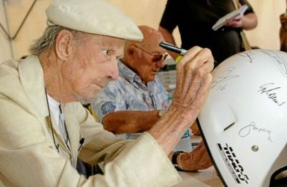 Submitted photo Racing legend John Fitch signs an autograph for a fan. Fitch, 95, died Wednesday at his home in Lime Rock.