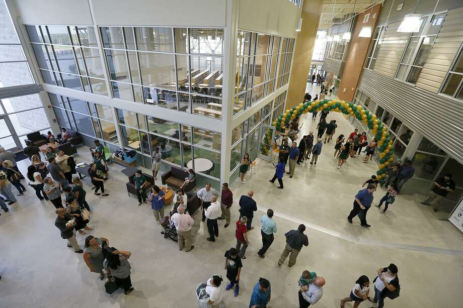 People meander around the entrance of Southwest Legacy High School after a dedication ceremony held Aug. 10. The school opened for classes Monday along with the area's other new high school, Harlan High School. Photo: Edward A. Ornelas /San Antonio Express-News / © 2017 San Antonio Express-News