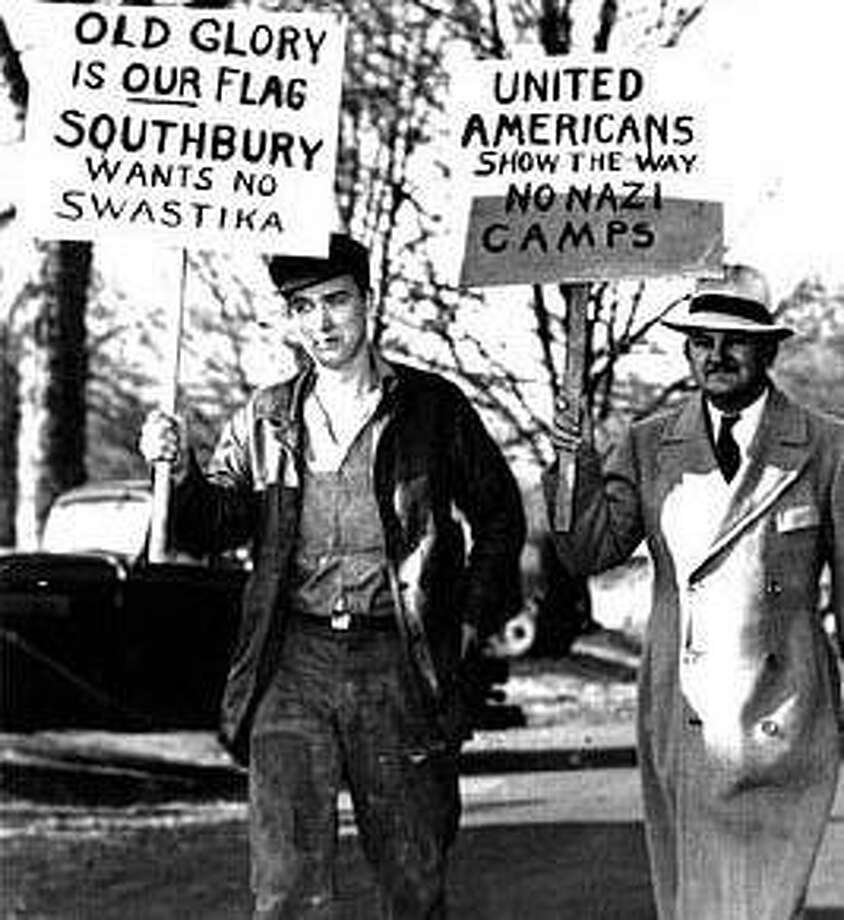 """Southbury residents Ernest Moeller, left, and Robert Harrison carry signs in front of the town's Community Hall in 1937. From the Web site of the Southbury Historical Society, <a href=""""http://www.southburyhistory.org"""">www.southburyhistory.org</a>."""