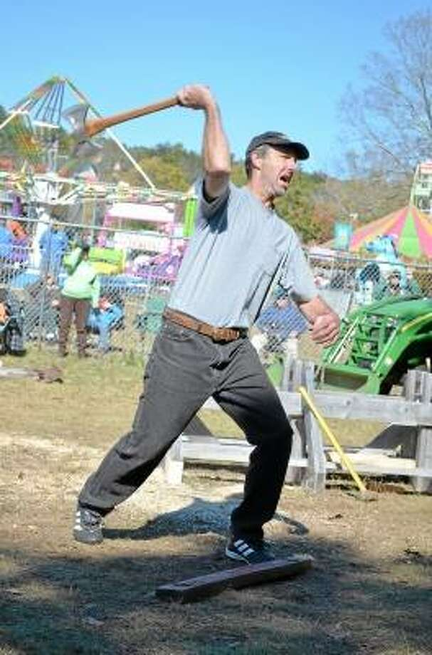 John Berry/Register Citizen Tom Kass of Holyoke, Mass., displays an uncommon one-handed throwing style in the ax throwing competiton at the Riverton Fair on Saturday.