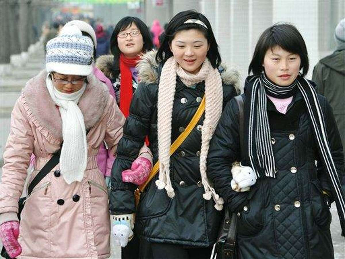 """Young North Korean women walk together Saturday, Jan. 1, 2011 in Pyongyang, North Korea. North Korea welcomed the new year Saturday with a call for better ties with rival South Korea, warning that war """"will bring nothing but a nuclear holocaust."""" (AP Photo/Kyodo News)"""