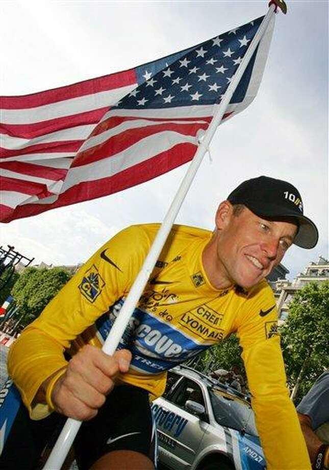FILE - In this July 24, 2005  file photo, Lance Armstrong, of Austin, Texas, carries the United States flag during a victory parade on the Champs Elysees avenue in Paris, after winning his seventh straight Tour de France cycling race. The world may soon know what the U.S. Anti-Doping Agency has on Armstrong. USADA has said it had 10 former teammates ready to testify against Armstrong before he chose not to take his case to an arbitration hearing. The list likely includes previous Armstrong accusers Floyd Landis and Tyler Hamilton. (AP Photo/Peter Dejong, File) Photo: AP / AP