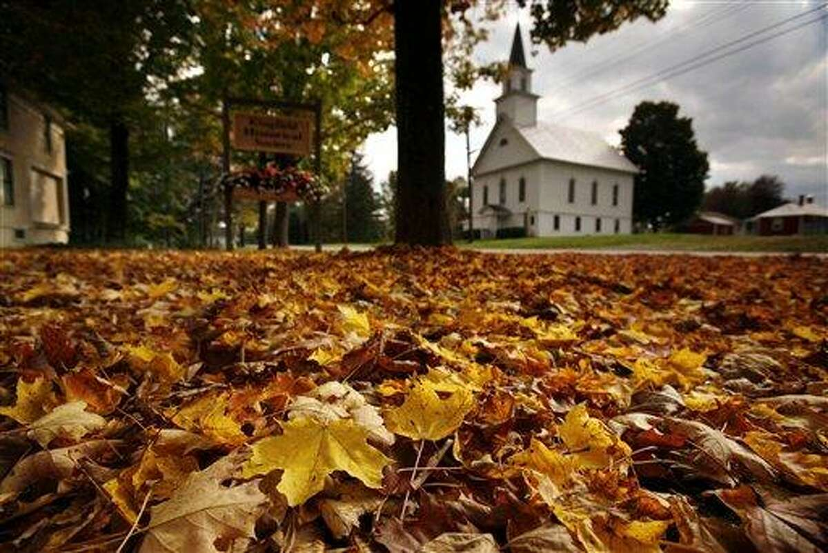 Fallen maple leaves carpet a lawn across the street from the First Baptist Church of Kingfield, Maine, Friday, Sept. 30, 2011. As trees start showing autumn's golden, orange and red hues, nature lovers aren't the only ones taking note: Scientists are watching trees and making note of time that leave change and drop as they seek to determine climate change's impact. (AP Photo/Robert F. Bukaty)