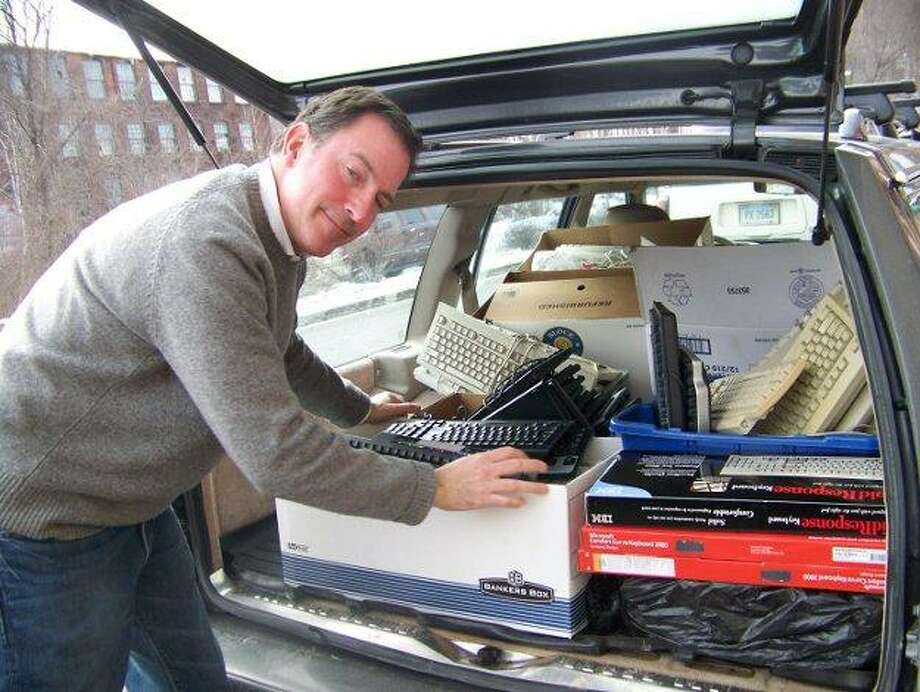 State Rep. John Rigby loads his car with donated computer keyboards, which he plans to send to troops overseas.