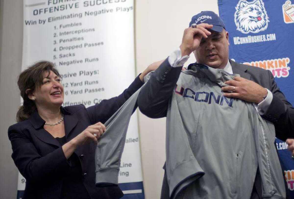 New University of Connecticut athletic director Warde Manuel, right, holds up a UConn shirt with help from university president Susan Herbst, left, during news conference in Storrs, Conn., Monday, Feb. 13, 2012. (AP Photo/Jessica Hill)