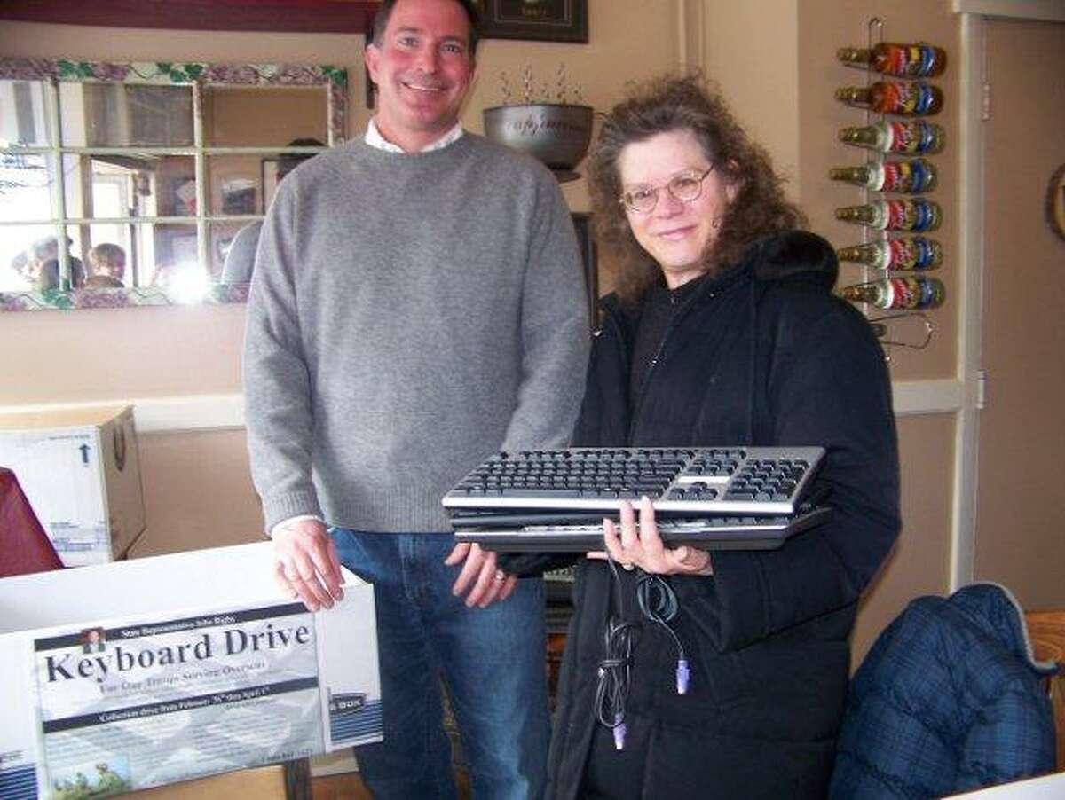 BARBARA THOMAS/Register Citizen Lois Orie, on behalf of Union Savings Bank's Operations Department in Litchfield, hands off a dozen keyboards to state Rep. John Rigby for his collection.