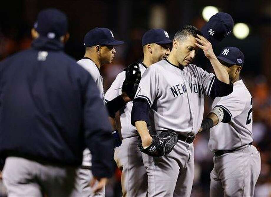 New York Yankees starting pitcher Andy Pettitte removes his cap as manager Joe Girardi, far left, walks out to relieve him in the eighth inning of Game 2 of the American League division baseball series against the Baltimore Orioles, Monday, Oct. 8, 2012, in Baltimore. Baltimore won 3-2. (AP Photo/Alex Brandon) Photo: AP / AP