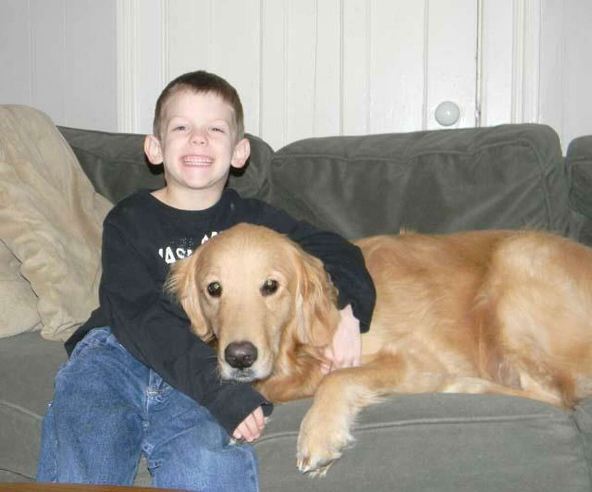 MIKE AGOGLIATI/ Register Citizen Tyler Bouteiller and his service dog Duncan pose for a picture at his house. The family is holding a benefit dinner to help raise funds to offset the cost of the service dog on March 28 at LaMonica's.