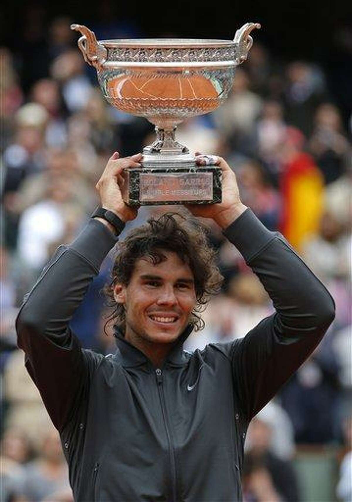 Spain's Rafael Nadal holds the cup after defeating Serbia's Novak Djokovic after their men's final match in the French Open tennis tournament at the Roland Garros stadium Monday in Paris. Nadal passes Bjorn Borg as the all-time record-holder for French Open titles. Associated Press