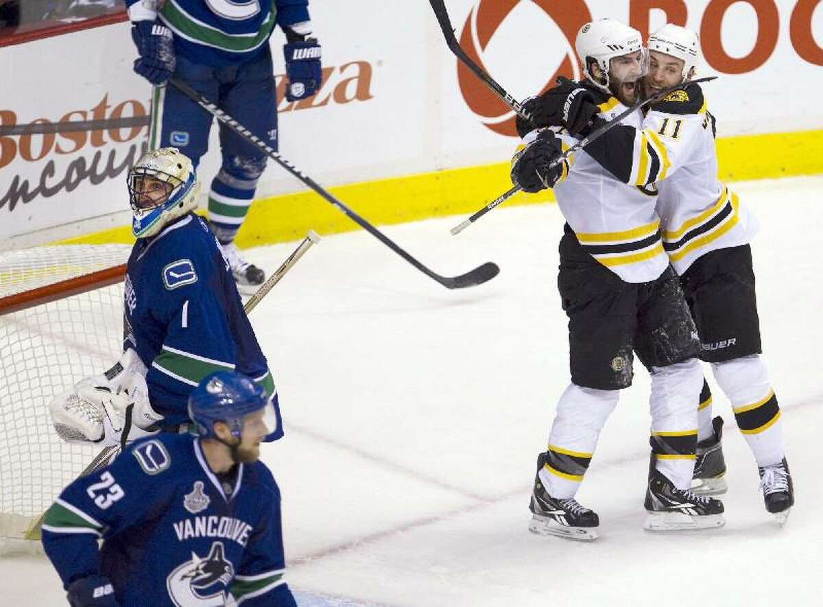 ASSOCIATED PRESS Boston Bruins center Patrice Bergeron celebrates with Gregory Campbell, right, after scoring on Vancouver Canucks goalie Roberto Luongo (1) as Canucks defenseman Alexander Edler (23) skates nearby during the second period of Game 7 of the Stanley Cup Finals on Wednesday in Vancouver, British Columbia.