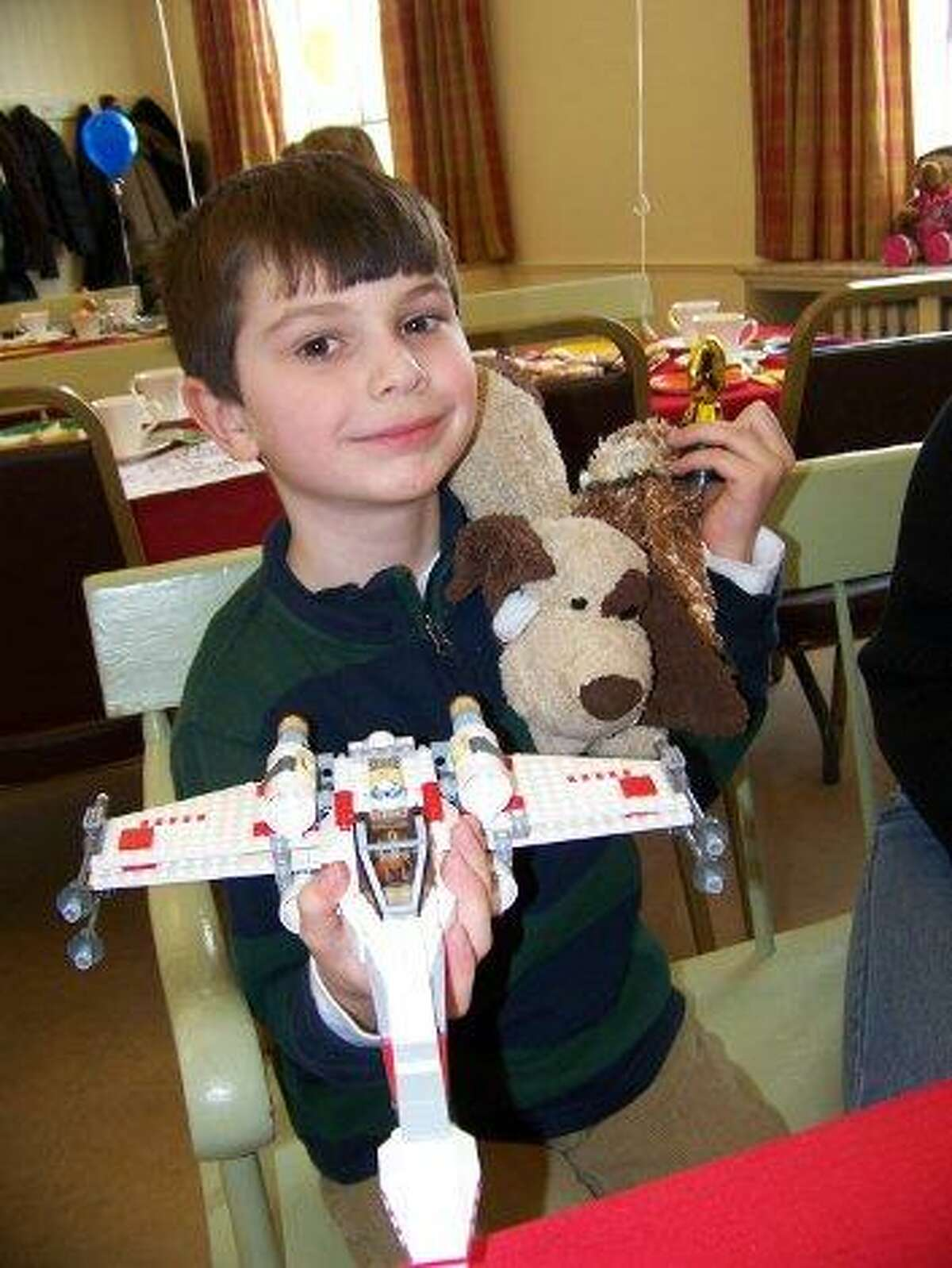 BARBARA THOMAS/Register Citizen Jacob Kuegler, 6-1/2, of Litchfield shows his trophy for winning the LEGO contest, along with his creation: a X-wing fighter from Star Wars.
