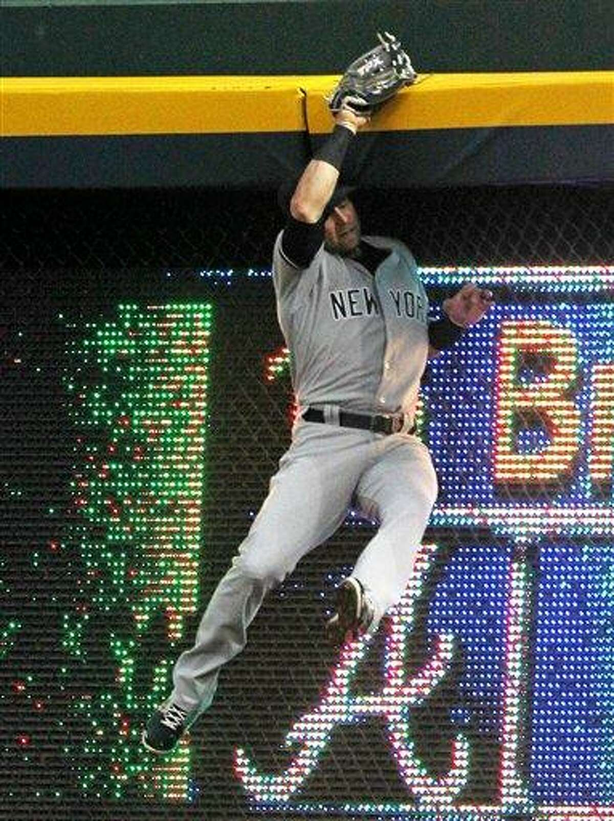 New York Yankees right fielder Nick Swisher makes a leaping catch against the wall on a hit by Atlanta Braves' Brian McCann preventing his homerun during an interleague baseball game in Atlanta on Monday, June 11, 2012. (AP Photo/Atlanta Journal & Constitution, Curtis Compton)