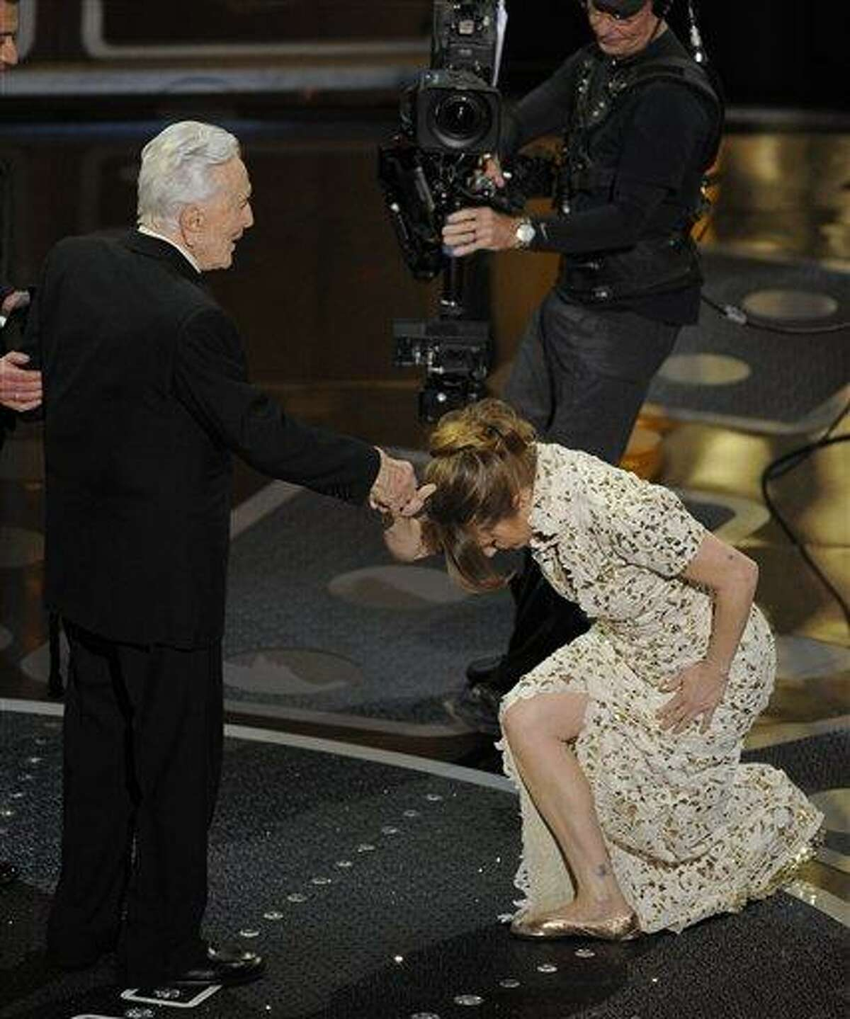 Melissa Leo bows to Kirk Douglass as she accepts the Oscar for best actress in a supporting role for