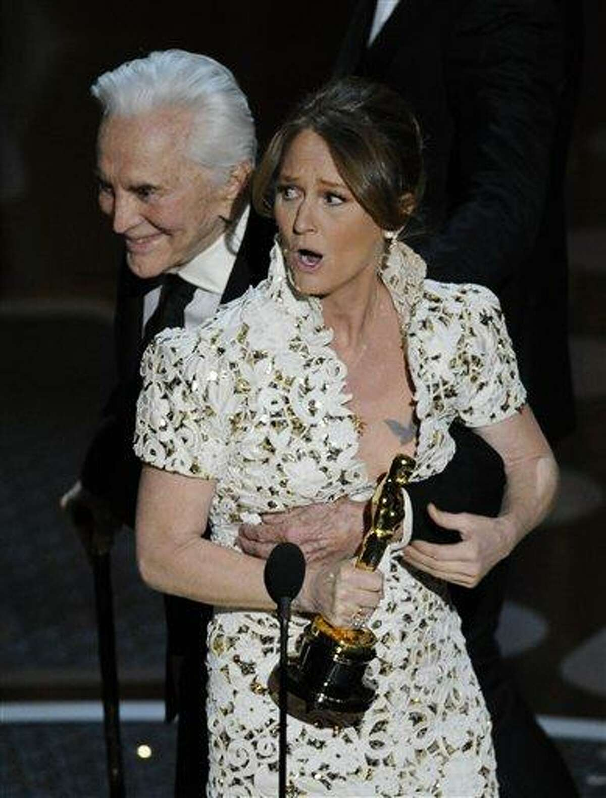 Melissa Leo gets a hug from Kirk Douglass as she accepts the Oscar for best actress in a supporting role for
