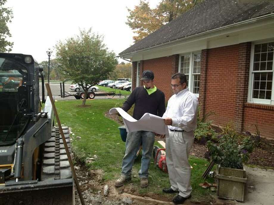 Sarah Bogues/The Register Citizen Tyler Reidhard, owner of T.R. Designs, and Harwinton First Selectman Mike Kriss look at blue prints for the sidewalk repair project at town hall.