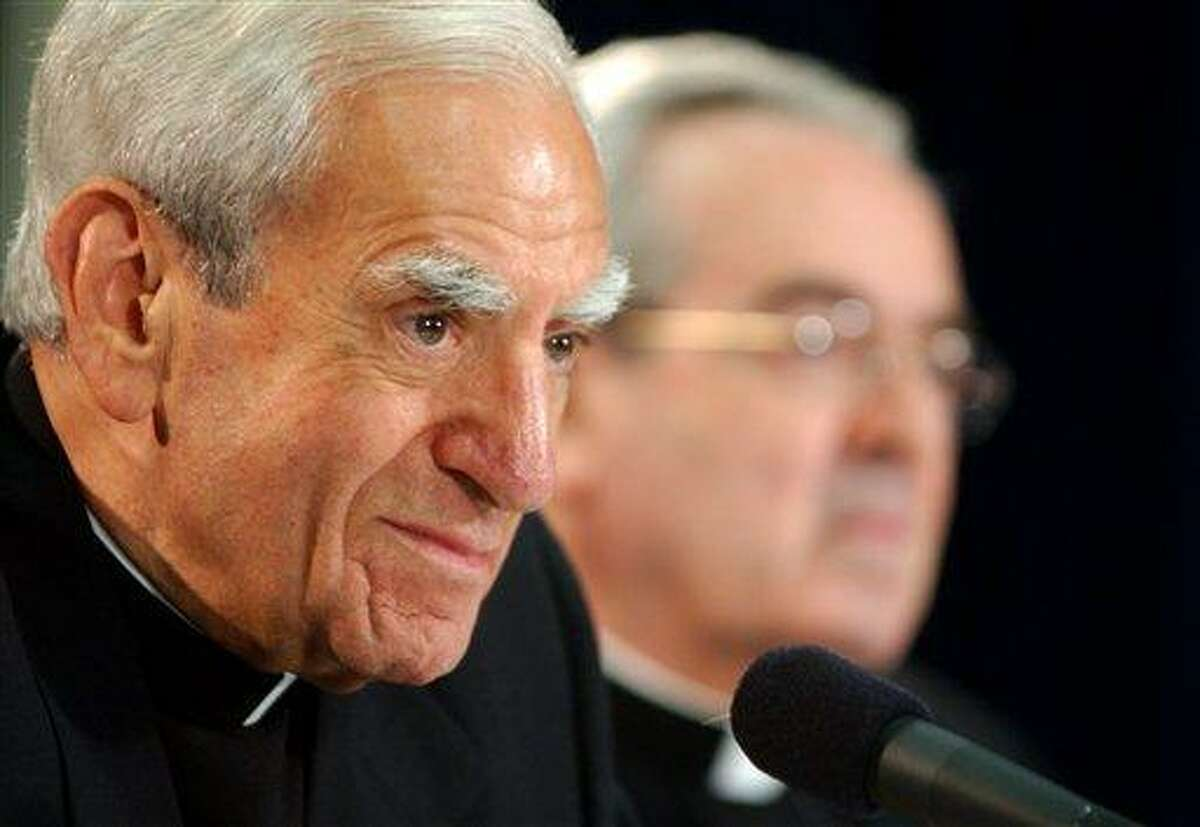 In this 2003 file photo, Cardinal Anthony J. Bevilacqua listens to a reporter's question as St. Louis Archbishop Justin F. Rigali, right, listens at a news conference in Philadelphia. The child-molestation scandal in the Archdiocese of Philadelphia has taken a mysterious new turn, with prosecutors asking a coroner to examine the body of Cardinal Anthony Bevilacqua to establish whether he died of natural causes. Associated Press