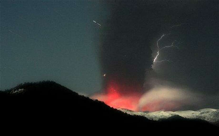 Lightning strikes over the Puyehue-Cordon Caulle volcano in Chile, seen from the international cross border way Cardenal Samore, in southern Chile, Sunday June 12, 2011. The volcano erupted June 4 after remaining dormant for decades. Chilean officials ordered most residents already evacuated from homes near the erupting volcano to stay in shelters and with family and friends Sunday due to the threat of deadly landslides. The ash spread across the Pacific, prompting authorities to suspend flights in Australia and New Zealand.  (AP Photo/Alvaro Vidal) Photo: AP / AP