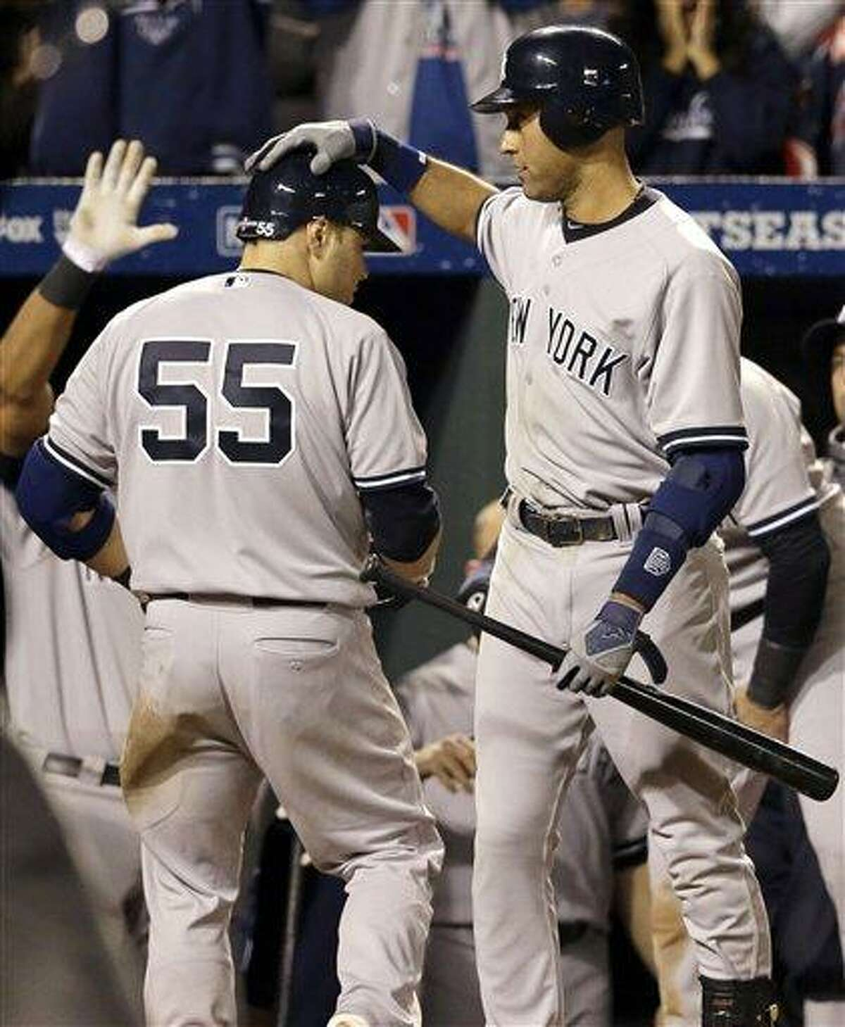 New York Yankees' Derek Jeter, right, congratulates teammate Russell Martin after Martin hit a solo home run in the ninth inning of Game 1 of the American League division baseball series against the Baltimore Orioles on Sunday, Oct. 7, 2012, in Baltimore. New York won 7-2. (AP Photo/Patrick Semansky)