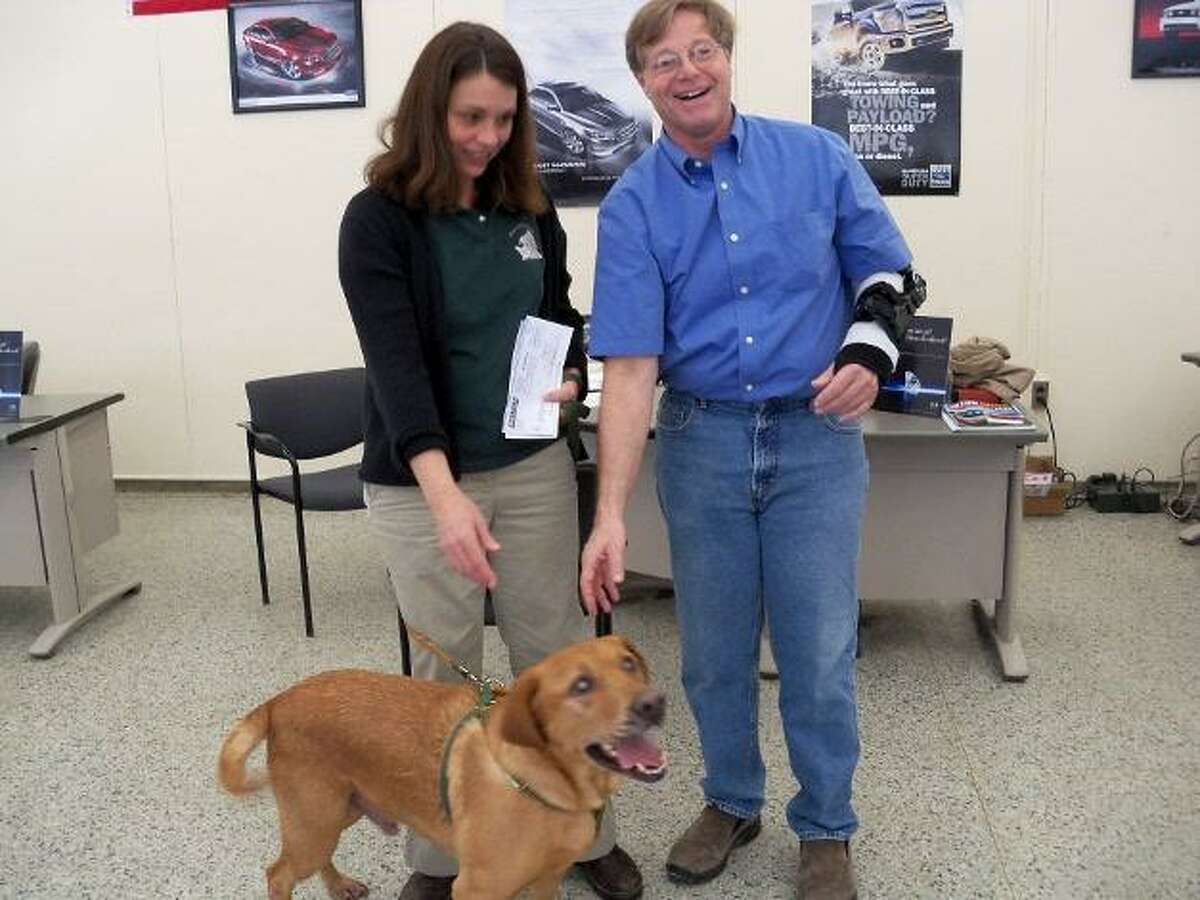 JENNY GOLFIN/Register Citizen Rob Lombard presents a check to a staff member of the Little Guild of St. Francis, along with Rusty, a dog available for adoption at the West Cornwall shelter.