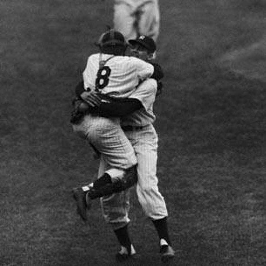 New York Yankees' catcher Yogi Berra leaps into the arms of pitcher Don Larsen after Larsen struck out the last Brooklyn Dodgers' batter to complete his perfect game during the fifth game of the World Series, Oct. 8, 1956.  Racing up in the background is Joe Collins. (AP Photo) Photo: AP / 1956 AP